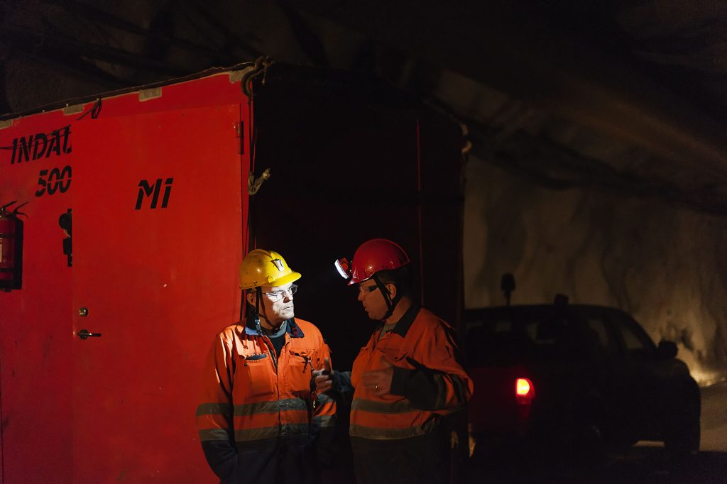 Two workers at night with headlamps talking in front of a battery storage unit.